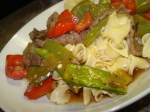 Beef with green and red peppers and snow peas on a bed of pasta on a white plate